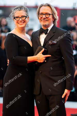 Gary Oldman, Gisele Schmidt. Actor Gary Oldman, right, and Gisele Schmidt poses for photographers upon arrival at the premiere of the film 'The Laundromat' at the 76th edition of the Venice Film Festival, Venice, Italy