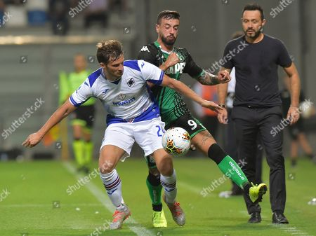 Sassuolo's Francesco Caputo, right, vies for the ball with Sampdoria's Bartosz Bereszynski, during the Serie A soccer match between Sassuolo and Sampdoria at the Mapei stadium, in Reggio Emilia, Italy