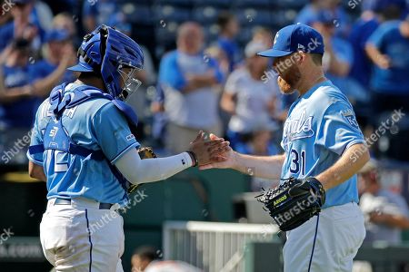 Kansas City Royals relief pitcher Ian Kennedy, right, and catcher Meibrys Viloria celebrate after a baseball game against the Baltimore Orioles, in Kansas City, Mo