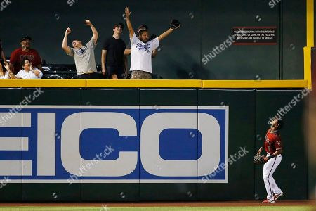 As Los Angeles Dodgers fans cheer, Arizona Diamondbacks center fielder Jarrod Dyson (1) watches a home run hit by Los Angeles Dodgers' David Freese clear the fence during the first inning of a baseball game, in Phoenix