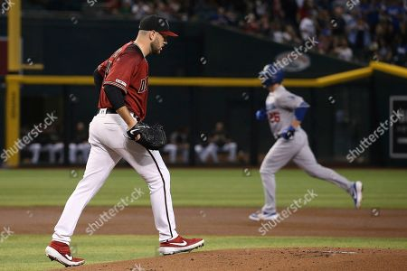 Arizona Diamondbacks starting pitcher Alex Young, left, walks back on the mound after giving up a home run to Los Angeles Dodgers' David Freese, right, during the first inning of a baseball game, in Phoenix