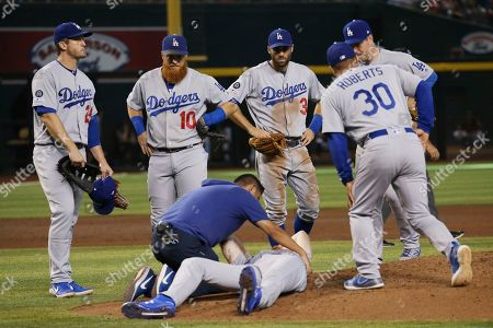 Los Angeles Dodgers medical staff Yosuke Nakajima, bottom left, attends to relief pitcher Dustin May, front, after May was hit by a batted ball from Arizona Diamondbacks' Jake Lamb during the fourth inning of a baseball game, in Phoenix. Dodgers' David Freese, left, Justin Turner (10), Chris Taylor (3), Dave Roberts (30) and Jedd Gyorko, right, all look on