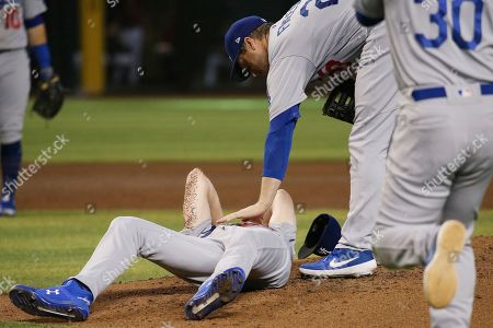 Los Angeles Dodgers relief pitcher Dustin May, left, is comforted by Dodgers' David Freese, second from right, as manager Dave Roberts (30) runs on the field during the fourth inning of a baseball game, after May was hit by a batted ball from Arizona Diamondbacks' Jake Lamb, in Phoenix
