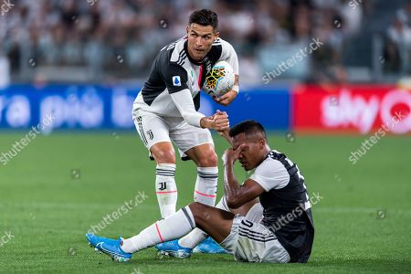 Cristiano Ronaldo of Juventus helps teammate Alex Sandro Lobo Silva up of the floor