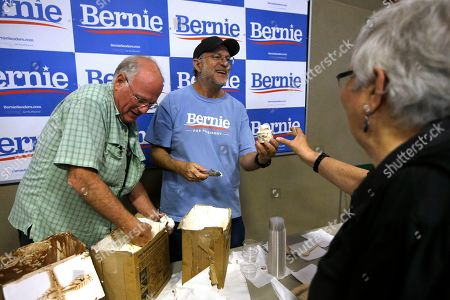 Ben & Jerry's co-founder Ben Cohen, left, and fellow co-founder Jerry Greenfield, center, scoop ice cream before a campaign event for Sen. Bernie Sanders, I-Vt., not shown, in Raymond, N.H