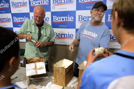 Ben & Jerry's co-founder Ben Cohen, center left, and fellow co-founder Jerry Greenfield, center right, scoop ice cream before a campaign event for Sen. Bernie Sanders, I-Vt., not shown, in Raymond, N.H
