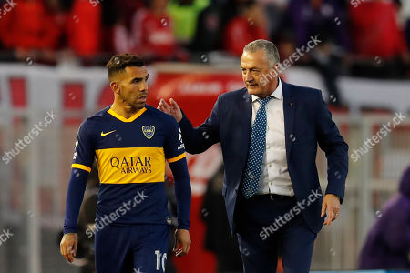 Boca Juniors' Carlos Tevez, left, is ready to substitute Alexis Mac Allister, next to coach Gustavo Alfaro, during an Argentine first division soccer game against River Plate in Buenos Aires, Argentina
