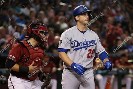 Los Angeles Dodgers' David Freese (25) strikes out as Arizona Diamondbacks catcher Alex Avila, left, heads to the dugout during the third inning of a baseball game, in Phoenix