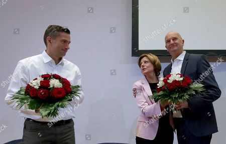 Malu Dreyer, acting co-chairwomen of the German Social Democratic Party (SPD), center, hands over bunches of flowers to Dietmar Woidke, top candidate of Brandenburg's Social Democratic Party (SPD), right, and Martin Dulig, top candidate of Saxony's Social Democratic Party (SPD), left, prior to a party's board meeting in Berlin, Germany, one day after the federal state elections in the German states of Saxony and Brandenburg