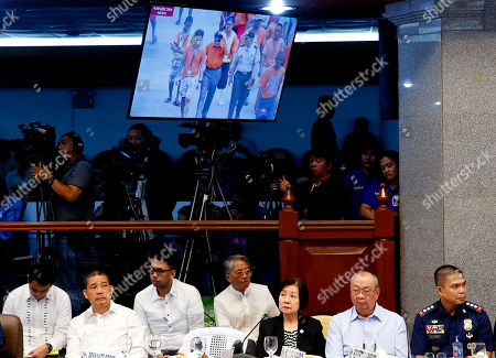 """Maria Clara Sarmenta, Roberto Sarmenta. Maria Clara Sarmenta, third from right, and husband Roberto Sarmenta, second from right, parents of slain student Eileen Sarmenta, listen to testimonies during the Senate probe on the failed release of former Mayor Antonio Sanchez (projected on the screen monitor above), who was convicted in the rape and murders in 1993 of Eileen and another student Allan Gomez, in suburban Pasay city south of Manila, Philippines. Calls are mounting for Bureau of Corrections Chief Nicanor Faeldon's resignation after his office allegedly permitted the release of nearly 2,000 convicted heinous criminals, including Sanchez, whose actions are not covered by the """"Good Conduct Time Allowance"""" law. At right is her husband Roberto Sarmenta"""