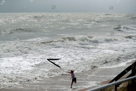 Stock Photo of Weston Lee, of Vero Beach, throws a piece of wood into the high surf from the Atlantic Ocean, in advance of the potential arrival of Hurricane Dorian, in Vero Beach, Fla