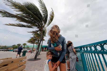 Stock Image of Kristen Davis watches the high surf from a boardwalk overlooking the Atlantic Ocean with her daughter Addie Davis 4, as winds from Hurricane Dorian blow the fronds of a palm tree palm tree, in Vero Beach, Fla