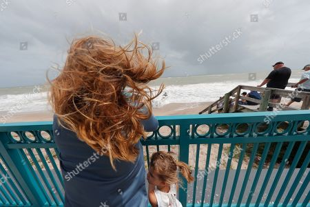 Stock Photo of Kristen Davis watches the high surf from a boardwalk overlooking the Atlantic Ocean with her daughter Addie Davis 4, as winds from Hurricane Dorian blow the fronds of a palm tree palm tree, in Vero Beach, Fla