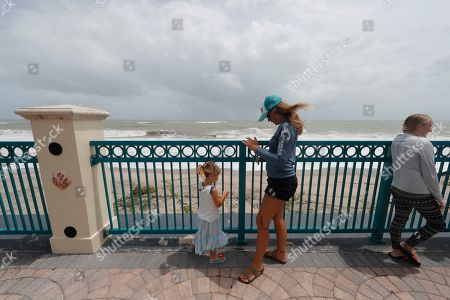 Kristen Davis watches the high surf from a boardwalk overlooking the Atlantic Ocean with her daughter Addie Davis 4, as winds from Hurricane Dorian blow the fronds of a palm tree palm tree, in Vero Beach, Fla