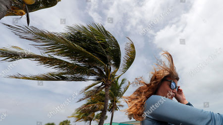 Kristen Davis watches the high surf from a boardwalk overlooking the Atlantic Ocean, as winds from Hurricane Dorian blow the fronds of a palm tree in Vero Beach, Fla