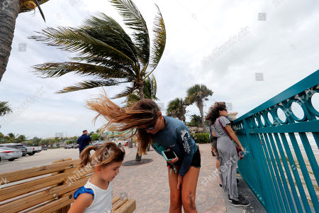 Kristen Davis watches the high surf from a boardwalk overlooking the Atlantic Ocean with her daughter Addie Davis, 4, as winds from Hurricane Dorian blow the fronds of a palm tree in Vero Beach, Fla