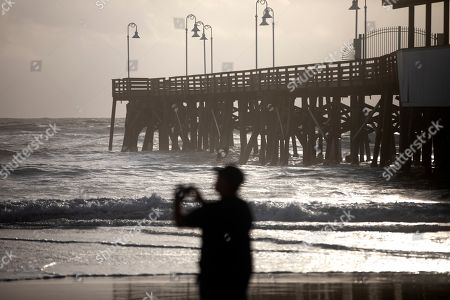 A beachgoer photographs the ocean alongside the Main Street Pier in Daytona Beach, Florida, USA, 02 September 2019. Hurricane Dorian, which made landfall on the Bahamas as category 5, caused 'unprecedented' devastation, according to Prime Minister Hubert Minnis. It is now downgraded to category 4 on route to pass to the east of Florida in the upcoming days.