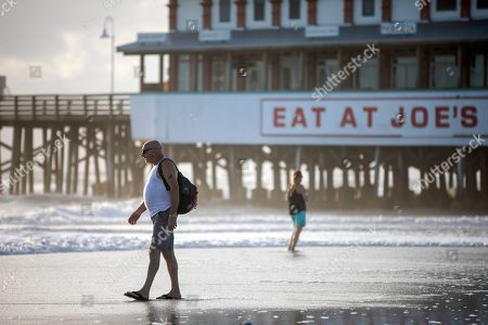 Beachgoers walk through rising surf next to the Main Street Pier in Daytona Beach, Florida, USA, 02 September 2019. Hurricane Dorian, which made landfall on the Bahamas as category 5, caused 'unprecedented' devastation, according to Prime Minister Hubert Minnis. It is now downgraded to category 4 on route to pass to the east of Florida in the upcoming days.