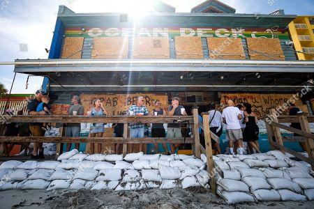 Patrons socialize on a deck surrounded by sandbags at the Ocean Deck Restaurant and Beach Club in Daytona Beach, Florida, USA, 02 September 2019. Hurricane Dorian, which made landfall on the Bahamas as category 5, caused 'unprecedented' devastation, according to Prime Minister Hubert Minnis. It is now downgraded to category 4 on route to pass to the east of Florida in the upcoming days.