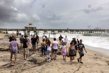 Beachgoers walk next to the ocean alongside the Juno Beach Pier in Juno Beach, Florida, USA, 02 September 2019. Hurricane Dorian, which made landfall on the Bahamas as category 5, caused 'unprecedented' devastation, according to Prime Minister Hubert Minnis. It is now downgraded to category 4 on route to pass to the east of Florida in the upcoming days.