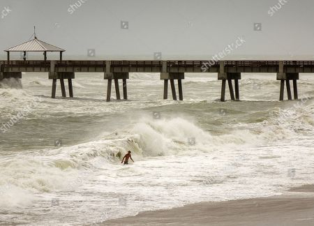 Beachgoers play in high waves next to the Juno Beach Pier in Juno Beach, Florida, USA, 02 September 2019. Hurricane Dorian, which made landfall on the Bahamas as category 5, caused 'unprecedented' devastation, according to Prime Minister Hubert Minnis. It is now downgraded to category 4 on route to pass to the east of Florida in the upcoming days.
