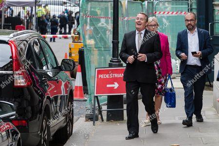 Liam Fox MP (L) arrives in Downing Street