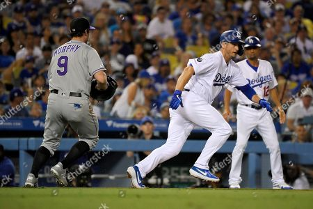 David Freese, Daniel Murphy. Los Angeles Dodgers' David Freese, center, runs back to third as Colorado Rockies first baseman Daniel Murphy chases him down after being caught between third and home during the fifth inning of a baseball game, in Los Angeles
