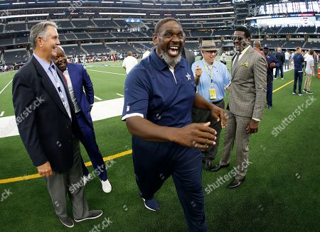 Stock Picture of Danny White, Emmitt Smith, Nate Newton, Brad Sham, Michael Irvin. Former Dallas Cowboys players, Danny White, Emmit Smith, left rear, Nate Newton, center, radio announcer Brad Sham, right rear, and Michael Irvin, right, joke around before a preseason NFL football game against the Tampa Bay Buccaneers in Arlington, Texas