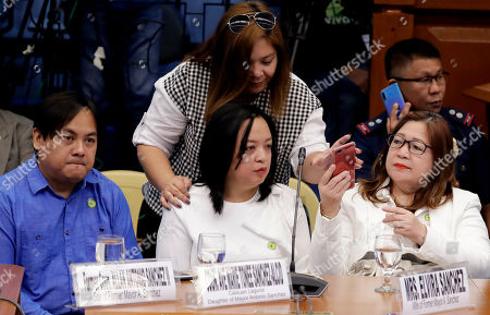"""Elvira Sanchez, Allan Antonio Sanchez, Ave Marie Tonee Sanchez, Marie Anton Elvie Sanchez. Elvira Sanchez, right, the wife of convicted former Mayor Antonio Sanchez, talks with her children Allan Antonio, Ave Marie Tonee, center, and Marie Anton Elvie, standing behind, during the second day of the Senate probe in the failed attempt to release from prison the former Mayor, who was convicted in the rape and murders of two students in 1993 in suburban Pasay city south of Manila, Philippines. Calls are mounting for the resignation of Bureau of Corrections Chief Nicanor Faeldon after his office allegedly permitted the release of nearly 2,000 convicted heinous criminals whose actions are not covered by the """"Good Conduct Time Allowance"""" law"""