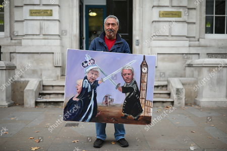 Artist Kaya Mar poses outside the Cabinet Office with a new piece of satirical artwork showing the Queen, Speaker John Bercow and Prime Minister Boris Johnson. MPs return from recess today and may vote on legislation to block a no deal exit from the European Union.