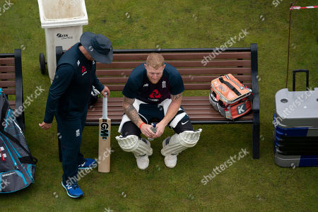 England's Ben Stokes, centre, speaks with coach Trevor Bayliss as he waits to bat during a nets session before the 4th Ashes Test cricket match between England and Australia at Old Trafford cricket ground in Manchester, England