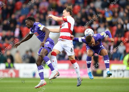 Freddie Ladapo of Rotherham United, Ben Sheaf of Doncaster Rovers and Carlton Morris of Rotherham United battle for the ball