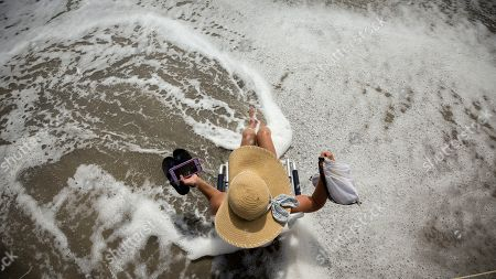 Resident and business owner Karen Kelly takes some time off to experience the heavy surf in advance of the Hurricane Dorian, in Tybee Island, Ga. The state issued a mandatory evacuation along the coast of Georgia on Sunday well before the storms expected arrival