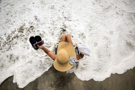 Resident and business owner Karen Kelly takes some time off to experience the heavy surf in advance of Hurricane Dorian, in Tybee Island, Ga. The state issued a mandatory evacuation along the coast of Georgia on Sunday well before the storm's expected arrival
