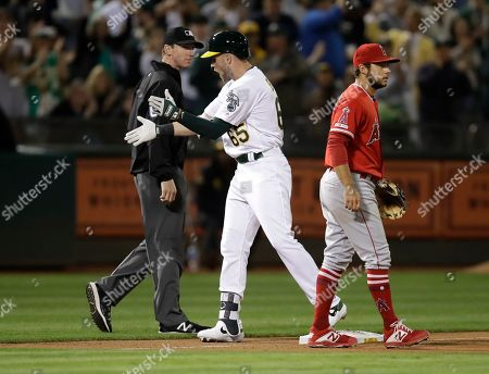 Stock Photo of Seth Brown, Alex Tosi, David Fletcher. Oakland Athletics' Seth Brown (65) celebrates between Los Angeles Angels' David Fletcher, right, and third base umpire Alex Tosi after hitting an RBI triple during the second inning of a baseball game, in Oakland, Calif