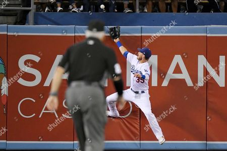 Cody Bellinger, David Rackley. Los Angeles Dodgers center fielder Cody Bellinger, right, can't reach a ball hit for a solo home run by Colorado Rockies' Daniel Murphy as second base umpire David Rackley watches during the second inning of a baseball game, in Los Angeles