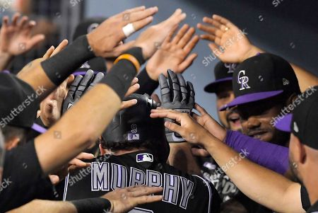 Colorado Rockies' Daniel Murphy is congratulated by teammates in the dugout after hitting a solo home run during the second inning of a baseball game against the Los Angeles Dodgers, in Los Angeles