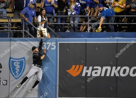Colorado Rockies center fielder Garrett Hampson can't reach a ball hit for a solo home run by Los Angeles Dodgers' David Freese during the seventh inning of a baseball game, in Los Angeles
