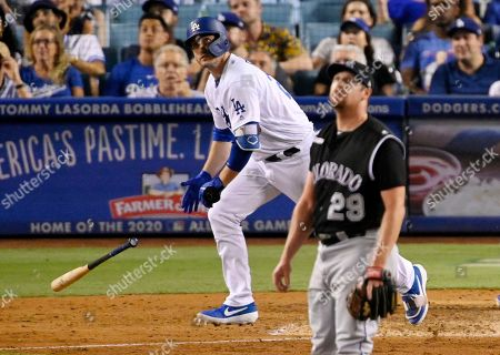 Stock Picture of David Freese, Bryan Shaw. Los Angeles Dodgers' David Freese runs to first after hitting a solo home run off Colorado Rockies relief pitcher Bryan Shaw, foreground, during the seventh inning of a baseball game, in Los Angeles