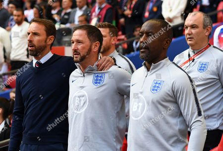 Gareth Southgate manager of England sings the national anthem alongside Steve Holland and Chris Powell