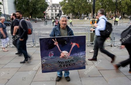 Satirical artist Kaya Mar holds up a painting outside the Houses of Parliament in Westminster, London.