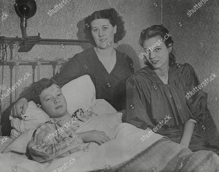 WWII: Neutral Shipping.The Dutch liner Simon Bolivar was sinking fast off the east coast, smashed on German mines. The official casualty list, given out last night, contains the names of 86 missing and killed. picture shows survivors: Two women, a boy, fellow passengers in the liner, are recuperating in North London. Miss Laura Martin (centre) - on her way to wed in Barbados - landed on top of 13-years-old Peter Wright-Nooth as she jumped into a lifeboat, is nursing him at her home since both his parents are in hospital. With them is Miss Margaret Ross, another survivor. She was on her way home to Trinidad