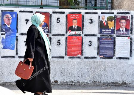 Woman walks at posters of Tunisian presidential candidates in the capital Tunis on September 2, 2019. Campaigning for Tunisia's presidential elections opened today with 26 candidates vying to replace late leader Beji Caid Essebsi in a vote seen as vital to defending democratic gains in the cradle of the Arab Spring.