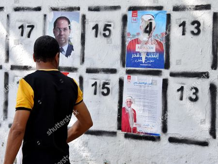 Man walks past posters of Tunisian presidential candidates in the capital Tunis on September 2, 2019. Campaigning for Tunisia's presidential elections opened today with 26 candidates vying to replace late leader Beji Caid Essebsi in a vote seen as vital to defending democratic gains in the cradle of the Arab Spring.