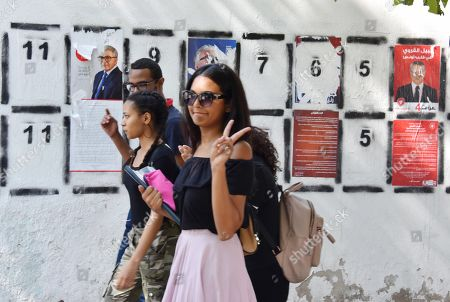 People pass posters of Tunisian presidential candidates in the capital Tunis on September 2, 2019. Campaigning for Tunisia's presidential elections opened today with 26 candidates vying to replace late leader Beji Caid Essebsi in a vote seen as vital to defending democratic gains in the cradle of the Arab Spring.