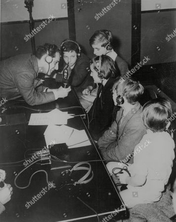 WWII: Britain: Evacuation. Children wearing earphones, speaking into a microphone from an American broadcasting studio. The children are evacuees from Britain. Picture shows: L-R: Announcer Ben Grauer, Michael Marcus, 13, Royston Marks, 15, Yvonne Burkitt, 12, George Weychan, 12, and John Arlingham Toye, four and a half