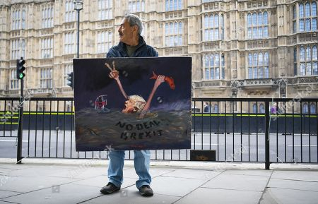 Political satire artist Kaya Mar with his painting of a drowning British Prime Minister Boris outside parliament in London, Britain, 04 September 2019. Members of Parliament will vote on a bill forcing Britain's Prime Minister Boris Johnson to delay Brexit unless MPs back a new deal or vote for a no-deal exit. The Prime Minister will table a motion to call for a general election if that bill passes.