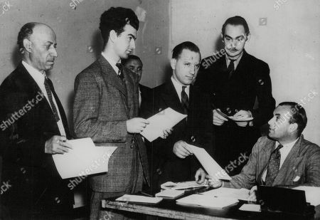 WWII: America.Hundreds of Americans in all parts of the United States have already applied for registration in answer to Britain's call for civilians to help in the work of radio location. picture shows: Mr Charles Cumming (right) handing out registration forms to applicants at the offices of the British consulate General on Broadway