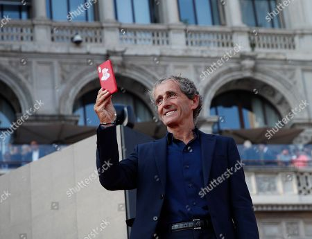 Alain Prost takes pictures of Ferrari fans as they attend an event to celebrate the 90th anniversary of the foundation, at Milan's Duomo square, Italy, . The F1 GP of Italy will take place at Monza race track, near Milan, Sunday