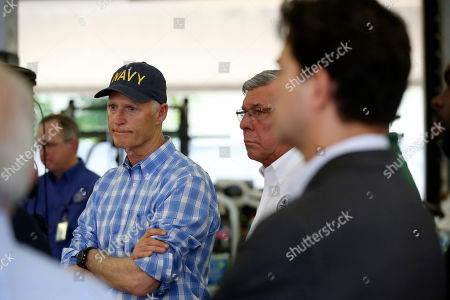 Sen. Rick Scott, R-Fla., left, listens as officials give a briefing to the news media at a fire station in Miami where relief supplies are being donated for those affected by Hurricane Dorian in the devastated Bahamian islands of Abaco and Grand Bahama, . Local churches are also accepting supplies in a relief effort spearheaded by descendants of some of Miami's earliest settlers from the Bahamas